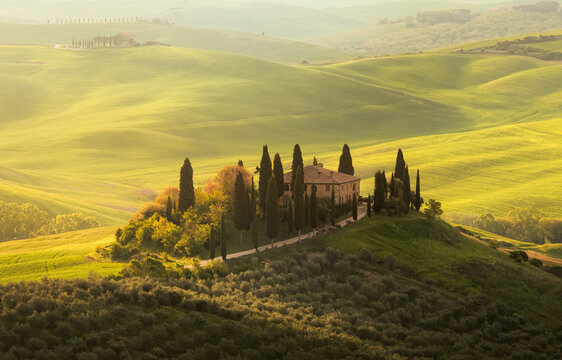 San Quirico d'Orcia, Tuscany, Italy - may, 15, 2019. A lonely farmhouse between rolling hills in Tuscany, during spring, when the wheat is ready for harvest.