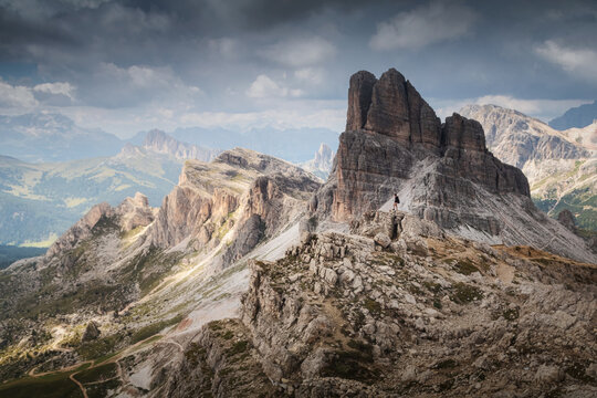 Dramatic view in dolomites on the peak Averau with man looking to the valley