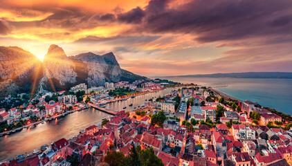 Gorgeous evening cityscape of old croatian resort - Omis town. Breathtaking summer seascape of Adriatic sea, Dalmatia coast, Croatia, Europe. Beautiful world of Mediterranean countries.