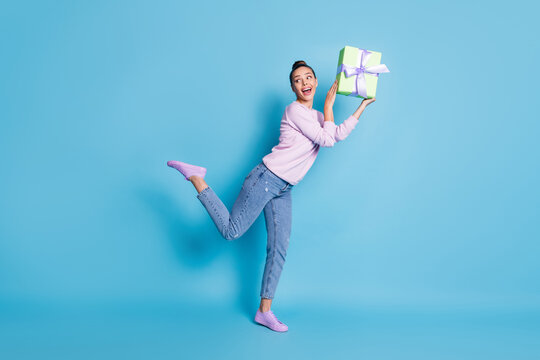 Full length photo of excited enthusiastic girl hold gift box enjoy rejoice anniversary celebration wear good look clothes sneakers isolated over blue color background