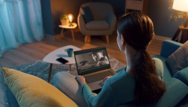 Woman resting on the sofa and connecting with her laptop