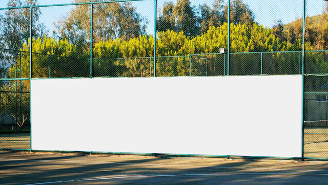 large blank white poster with mockup space hanging on metal fence of play ground