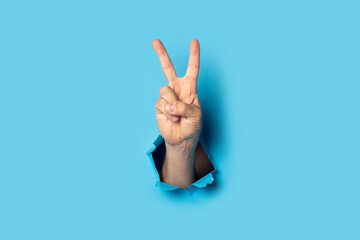 Fototapeta Male hand makes a two fingers up greeting gesture on a blue background. Banner obraz