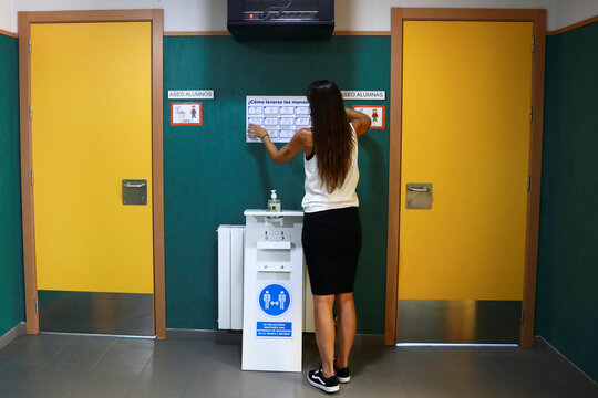 A teacher sets up a sign with instructions about coronavirus protocol in preparations of students' return to school, in Arganda del Rey