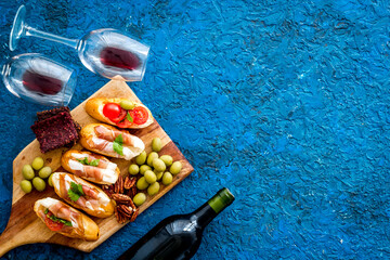 Fototapete - Wine appetizer. Toasts, nuts, olives on blue desk top view copy space