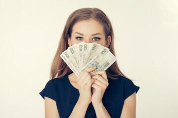 Anonimowa młoda kobieta trzyma gotówkę - kredyt, hipoteka, pożyczka, hazard, mieszkanie dla...