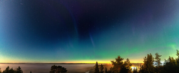 Panorama of Aurora borealis above foggy forest mountains. Northern lights. Sky with stars with polar lights above fog at beautiful landscape, city lights in low clouds at horizon line. Space.