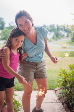 Little girl and mother with lit sparklers on July 4th