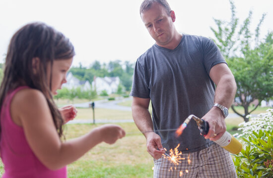 Father lights sparkler for timid little girl