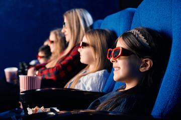Little friends wearing 3d eyeglasses in cinema.