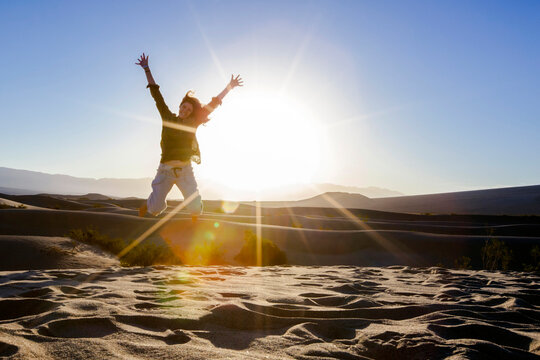 Woman Jumping on Sand Dune at Sunrise