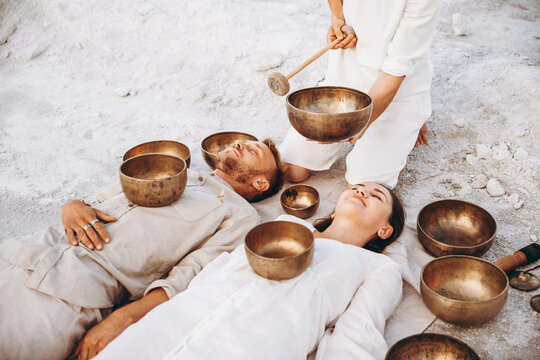 01.06.2019 Vinnitsa, Ukraine: group therapy with Tibetan singing bowls for a girl and a boy lying on the ground in the middle of the desert surrounded by copper bowls, meditation and relaxation