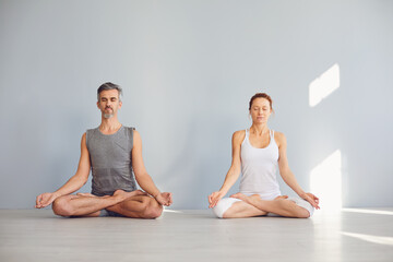 Yoga couple people hand sitting relaxation in lotus field on floor in studio class.
