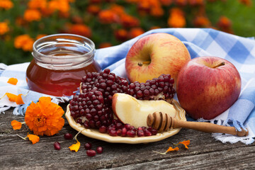 Rosh Hashanah holiday, greeting card with a jar of honey, pomegranate, apples, a plate with slices on an old wooden table in the garden against a background of flowers.