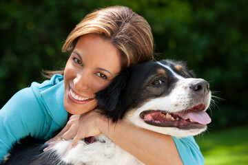 Portrait of middle aged Hispanic woman and her dog in backyard