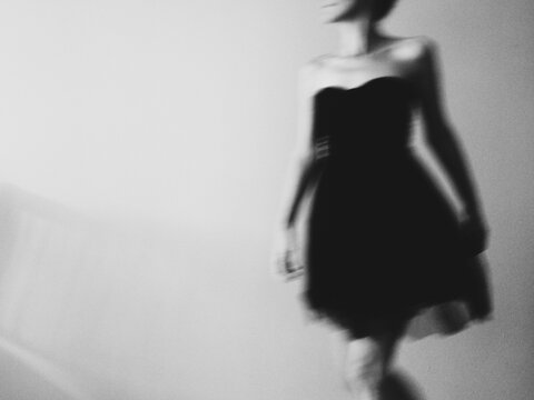 Unrecognisable woman, wearing a little black dress, moving swiftly