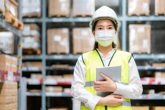 Young asian woman auditor or trainee staff wears mask working during the COVID pandemic in store warehouse shipping industrial. looking up and checks the number of items store by digital tablet.