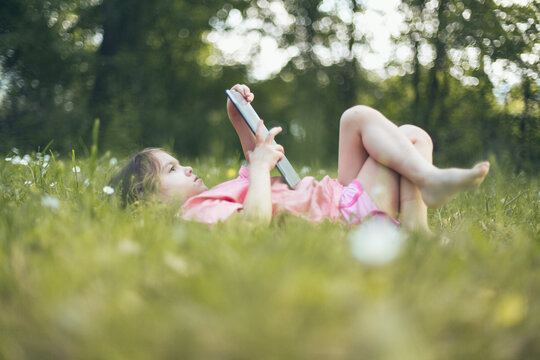 Child lying on grass ,reading on a digital tablet