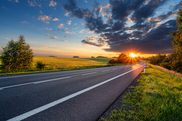 Fotobehang - Empty asphalt road in rural landscape in the rays of the sunset with dark storm cloud