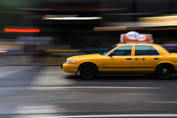 Yellow taxi in motion on a city street