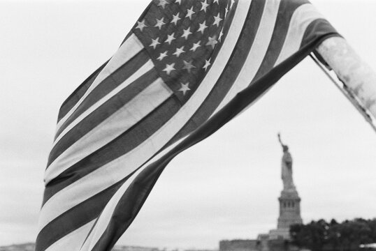 statute of liberty framed by american flag in black and white