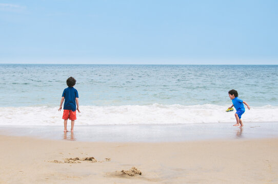 two little boys play a game of tag with the ocean at the beach