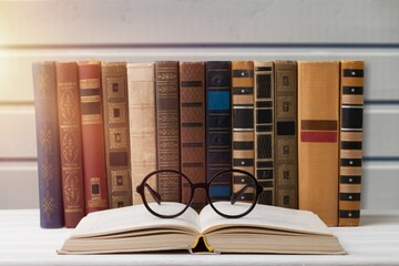 A stack of books with glasses for reading on the desk