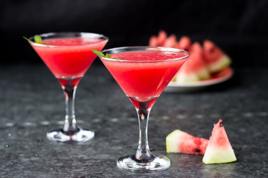 Cocktail in Martini glasses and watermelon. Triangular glasses with a pink drink inside and slices of watermelon