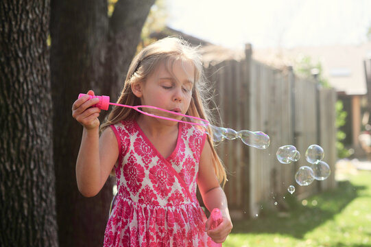 Young Girl Blows Bubbles in Pink Dress