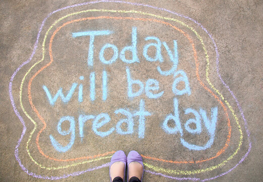 Feet standing by a chalk message that says Today will be a great day