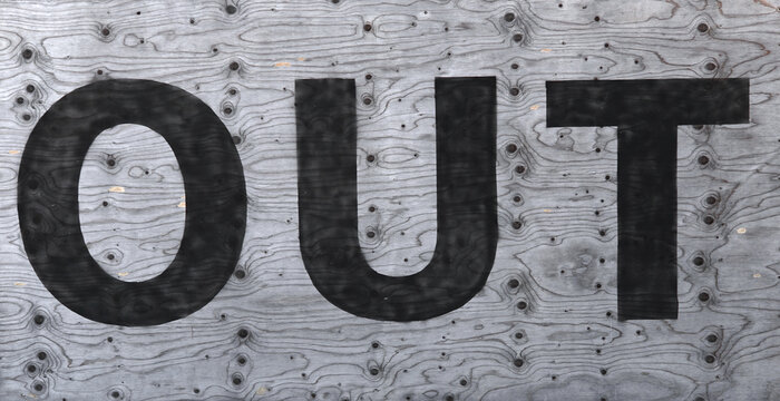 "The word """"OUT"""" painted on an old wooden panel"