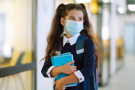 Schoolgirl in a protective mask with a backpack and a textbook in her hands. Security concept, virus protection. Covid-2019.