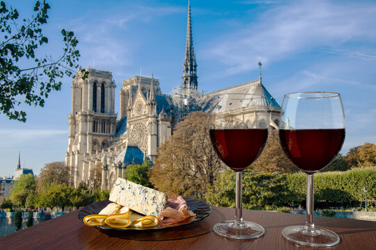 Two glasses of red wine with assortment of cheese and meat against Notre Dame de Paris or Notre-Dame Cathedral in Paris, France. Romantic celebration.