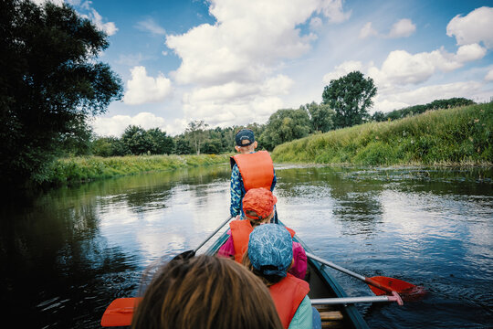 Familie auf Kanutour - Blick von hinten aus dem Kanu heraus