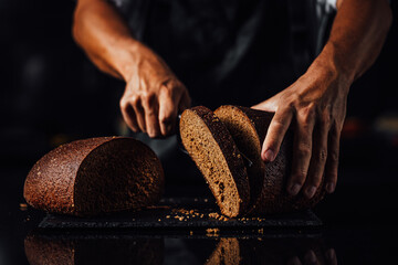 Man cutting whole grain bread on a stone board, dark background