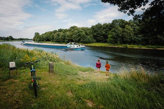 Zwei Kinder schauen einem Schiff auf der Ems hinterher
