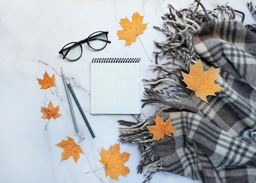 notepad, pencil, eyeglasses, autumn maple leaves and plaid. autumn still life, fall season concept. mock up. copy space