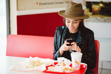 Young trendy woman using her phone at a fast food restaurant