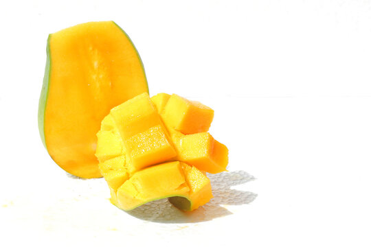 A Yellow mango chunks in squares on a white background