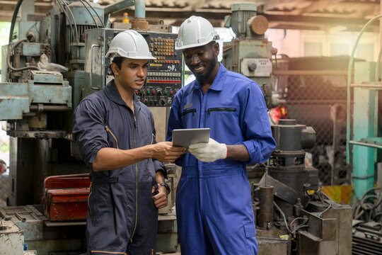 Multiethnic industrial engineers have to consult with colleagues while using a tablet. Supervisor, a worker with hard hat working in manufacturing factory on a business day. Concept of race equality