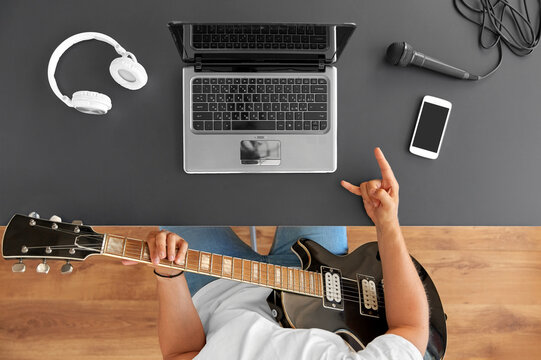 leisure, music and people concept - young man or musician with laptop computer playing guitar sitting at table