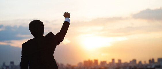 silhouette hand raised fist business man with sun lighting in morning.