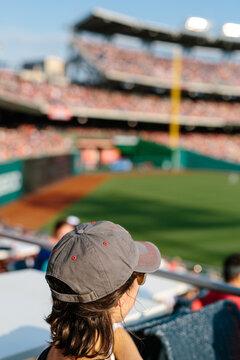 Woman in baseball cap watching professional game