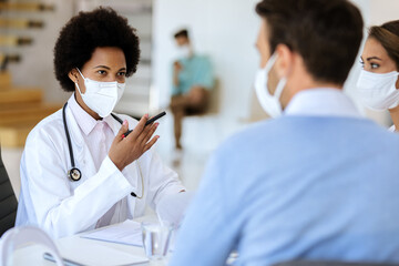 Black female doctor wearing face mask while talking to a couple at clinic.