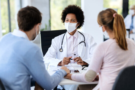 African American doctor wearing protective face mask during an appointment with a couple at clinic.