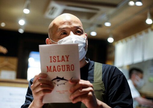 """Yasuyuki Shimahara, an owner of an """"izakaya"""" or Japanese style dining bar specializing in tuna dishes, shows off a leaflet of Islay Maguro in Tokyo"""