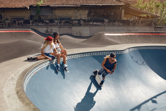 Summer. Skater Friends With Skateboard At Skatepark. Group Of People In Casual Outfit Outdoor. Hipster Girls Sitting On Concrete Ramp, Guy Skateboarding. Extreme Sport As Urban Lifestyle.