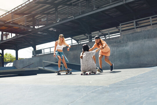 Subculture. Friends Skateboarding At Skatepark. Skater Man And Girls In Casual Outfit Having Fun Outdoor. Extreme Sport As Lifestyle Of Active Urban People.
