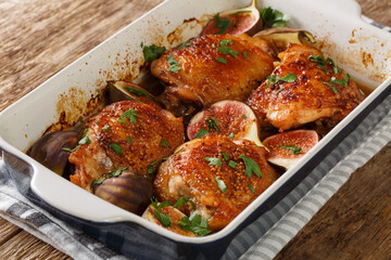 baked chicken thighs with figs and herbs close-up in a baking dish on the table. horizontal