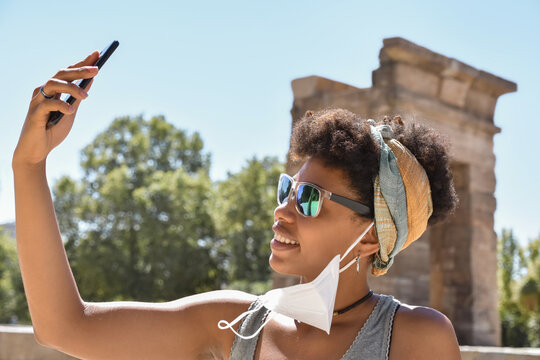 An african cutie, with a face mask hanging from the ear, using her phone for selfie and video chats during a cultural trip on a blurred monumental background. Cultural tourism in pandemic times.